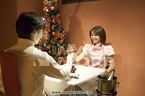Couple toasting at table in restaurant