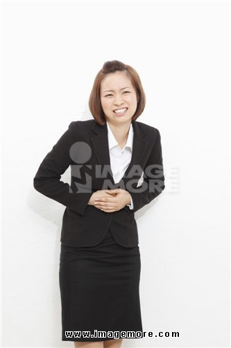 Young businesswoman suffering from stomachache