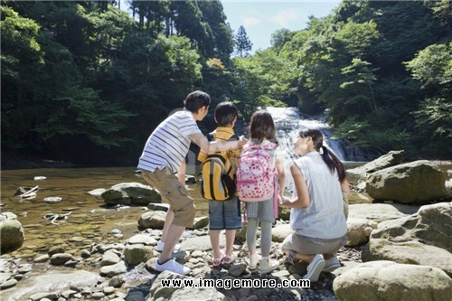 Family Standing by Mountain Stream