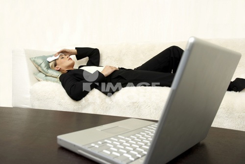 Business woman laying on the sofa with a headache