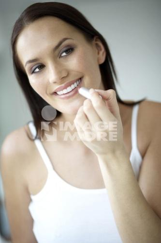 Woman applying make-up, close-up