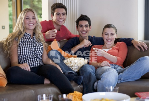 Four teenage friends watching television