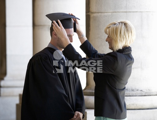 A mother checking her graduate son's gown