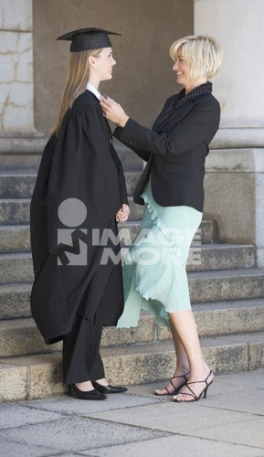 A mother checking her graduate daughter's gown