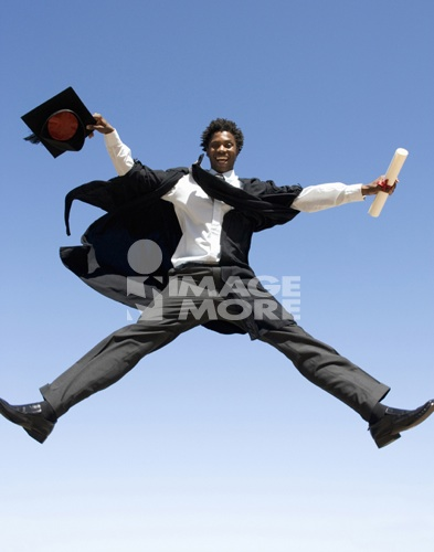 A graduate jumping for joy