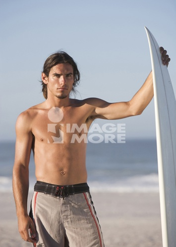 A surfer standing on a beach
