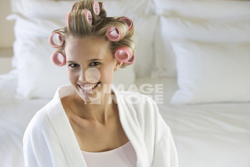 A young woman with her hair in curlers