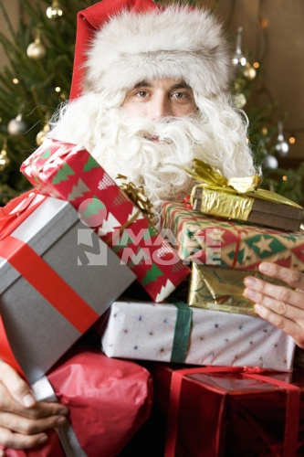 Father christmas / santa Claus holding a pile of presents