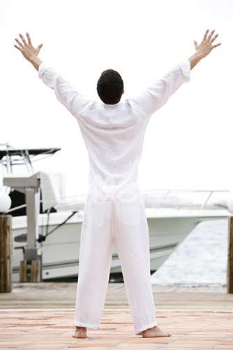 Man in white on a jetty by a boat, arms outstretched