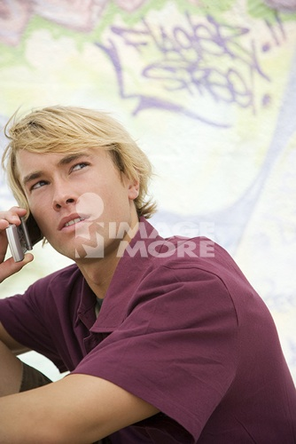 Portrait of a young man on a mobile telephone in front of a graffiti covered wall\n\n