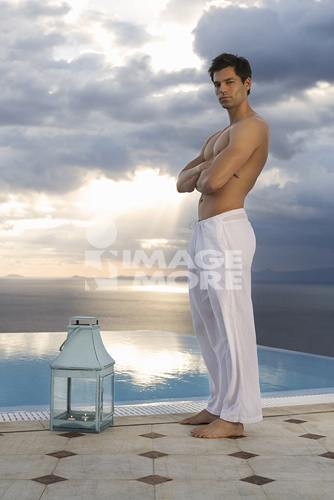 A man standing by a pool in the evening