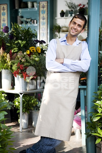 Male florist standing at the entrance to his shop