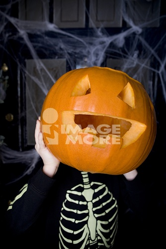 Child in a skeleton costume at a Hallowe'en party, holding a pumpkin with a carved face