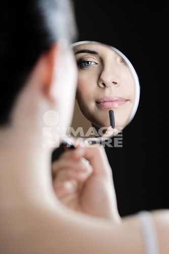 Reflection of young woman putting on lipstick in front of a mirror