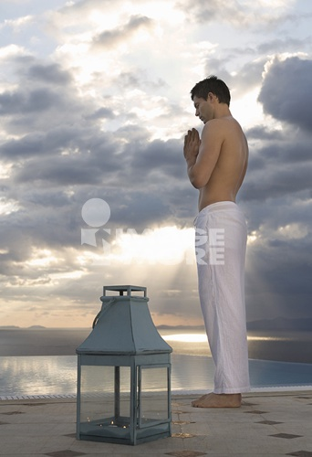 A man meditating by a pool