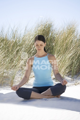 Young woman performing yoga on a beach