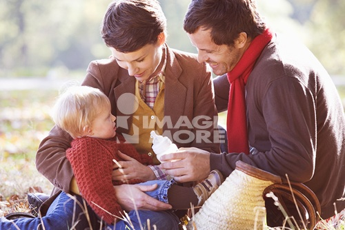 A young family sitting on the grass, father feeding the baby