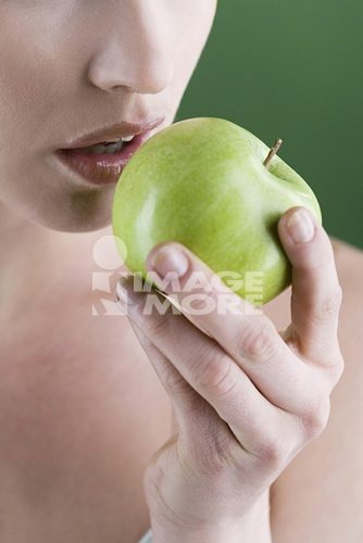 A young woman eating an apple, close-up