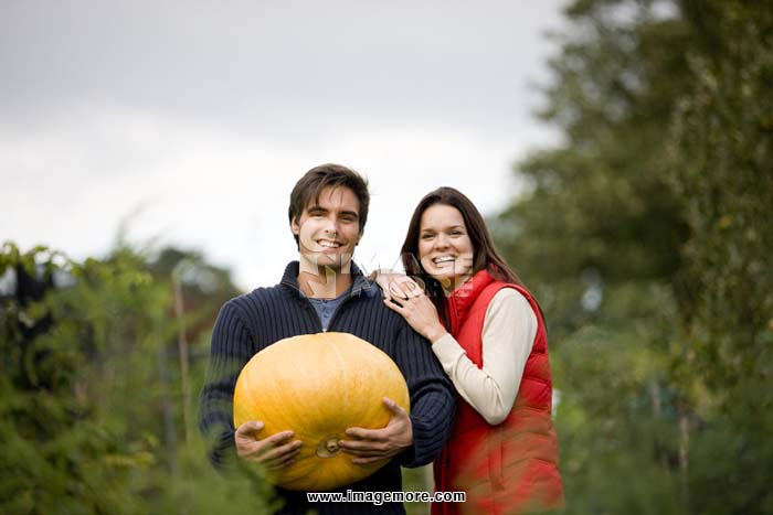 A young couple standing on an allotment, man holding a pumpkin
