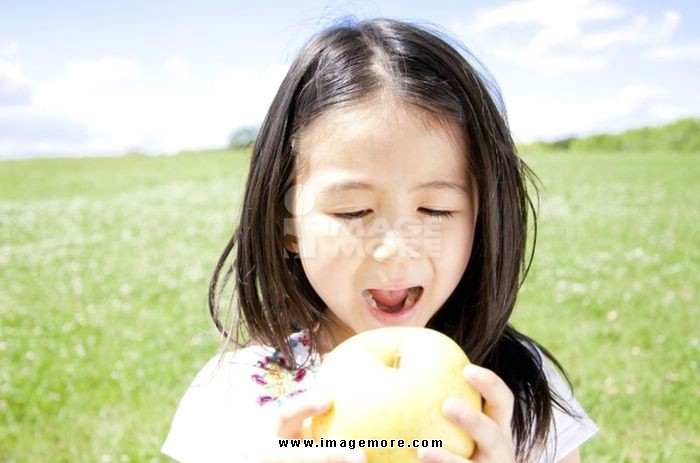Girl eating a green apple