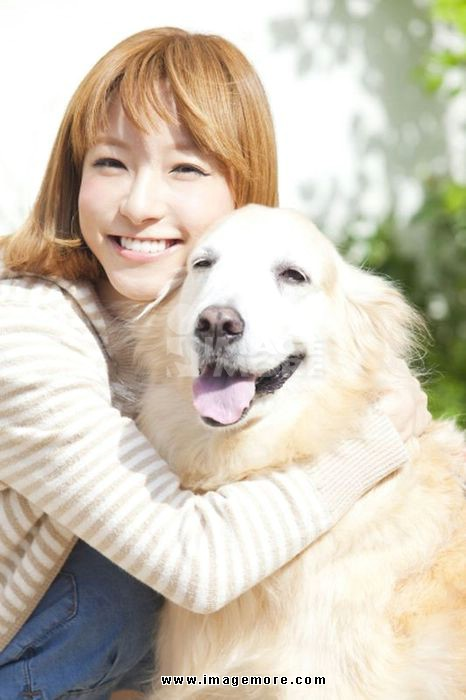 Smiling women embrace the Golden Retriever