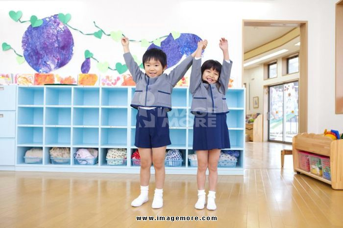 Men and women raise their hands in kindergarten children holding hands