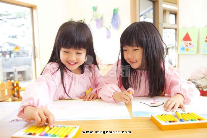 Two kindergarten girls draw with crayons