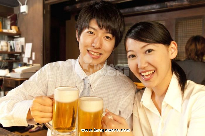 Businessman smiling and OL have a beer in a tavern