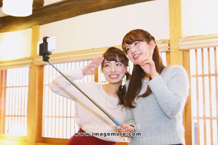 Two young Japanese women taking a selfie in Kawagoe old town, Japan,
