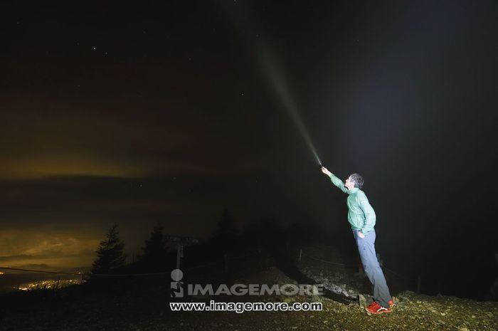 Caucasian man with torch on in the mountains at night,