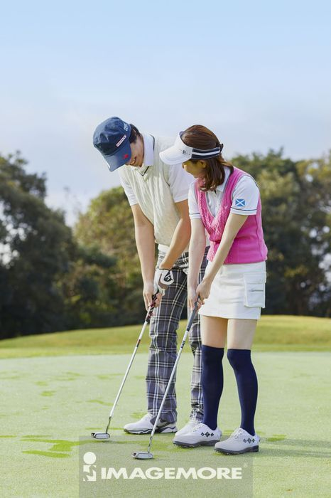 Japanese golf players on course,