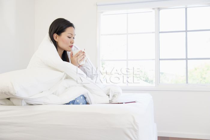 Chinese woman with coffee wrapped in a blanket on bed