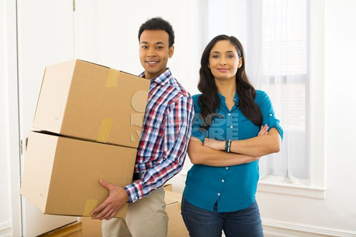 Mixed race couple carrying cardboard boxes in new home
