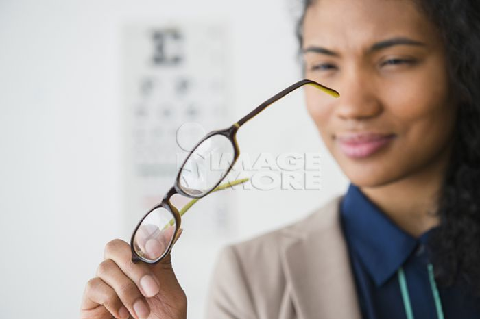 Mixed race woman examining eyeglasses