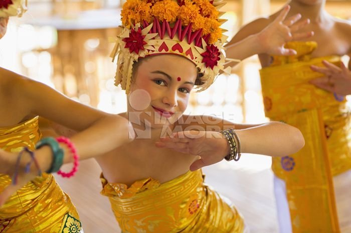 Caucasian girl dancing in traditional Balinese clothing