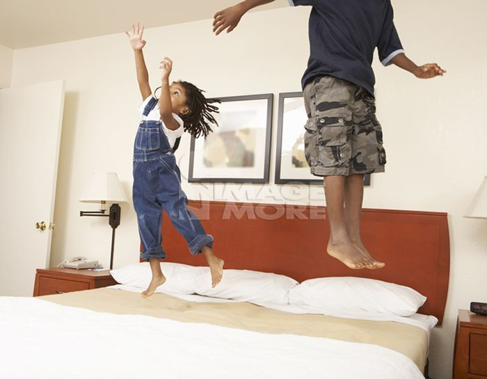 Black children jumping on bed