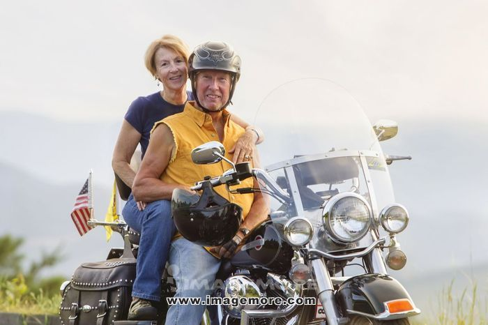 Older Caucasian couple smiling on motorcycle