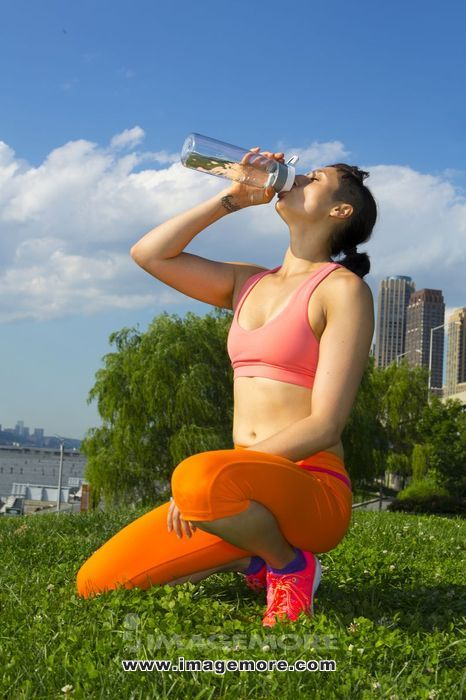 Mixed race woman drinking water in urban park