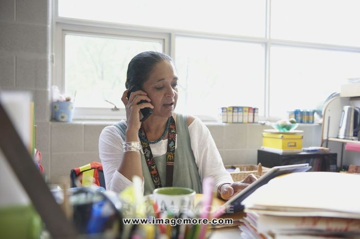 Indian teacher talking on cell phone at desk in classroom
