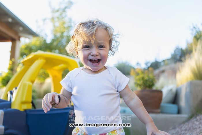 Caucasian boy laughing in backyard
