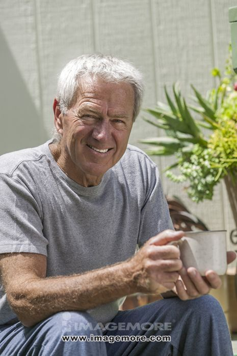 Smiling older man drinking coffee outdoors