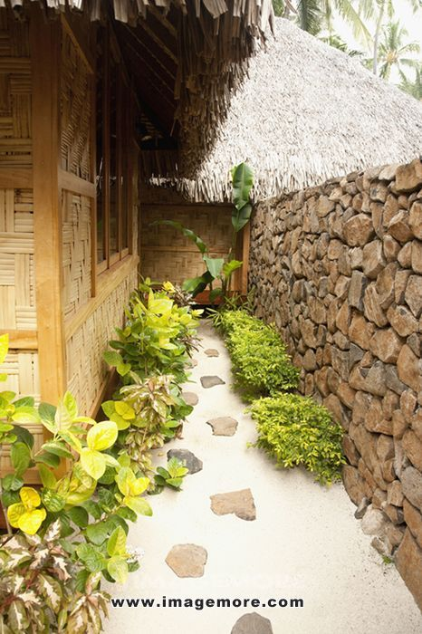 Rocks in sandy walkway behind hotel hut