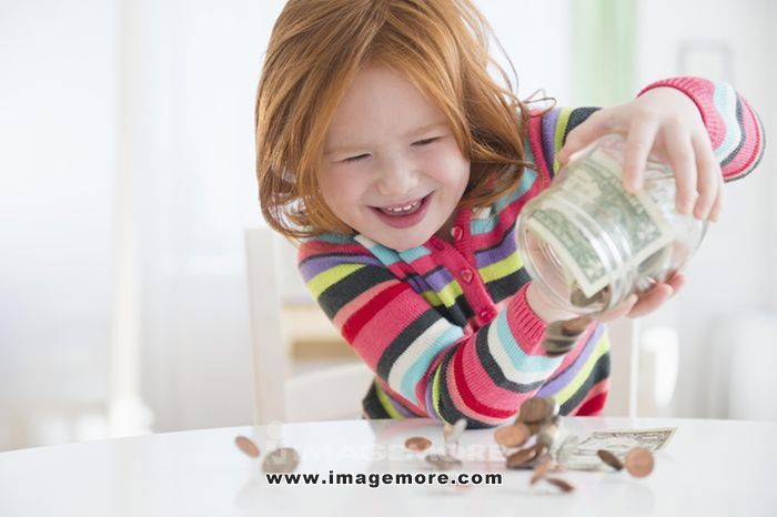 Caucasian girl pouring money from change jar
