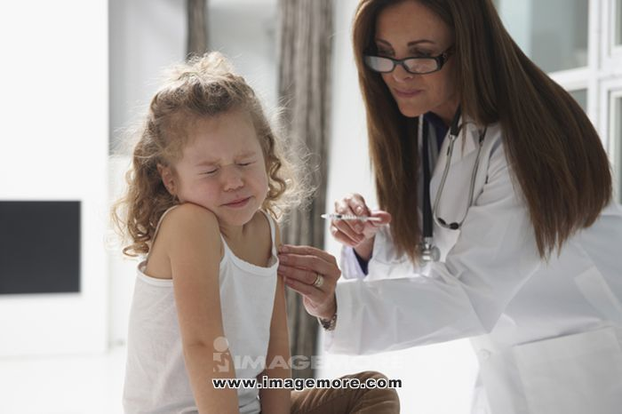 Caucasian doctor vaccinating girl