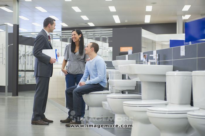 Salesman helping couple shopping for toilet in store
