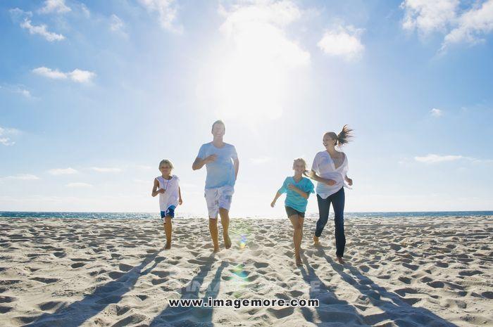 Caucasian parents and children running on beach