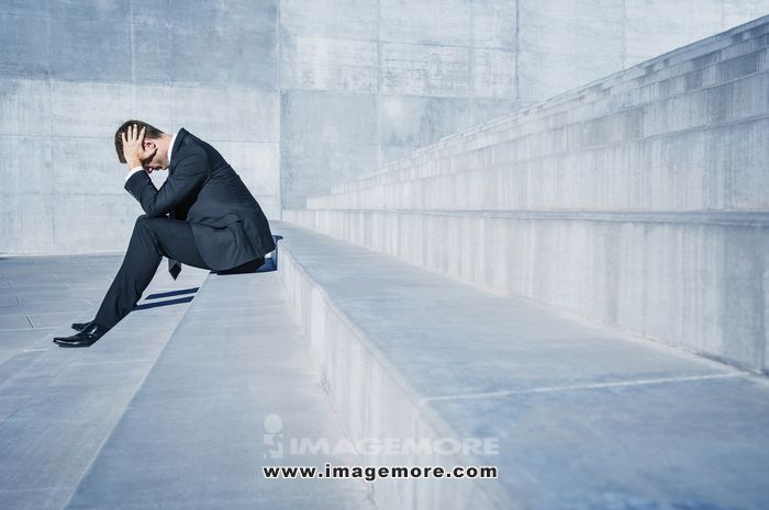 Stressed Caucasian businessman sitting on outdoor staircase