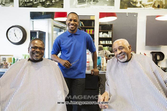 Black barber and customers smiling in retro barbershop,