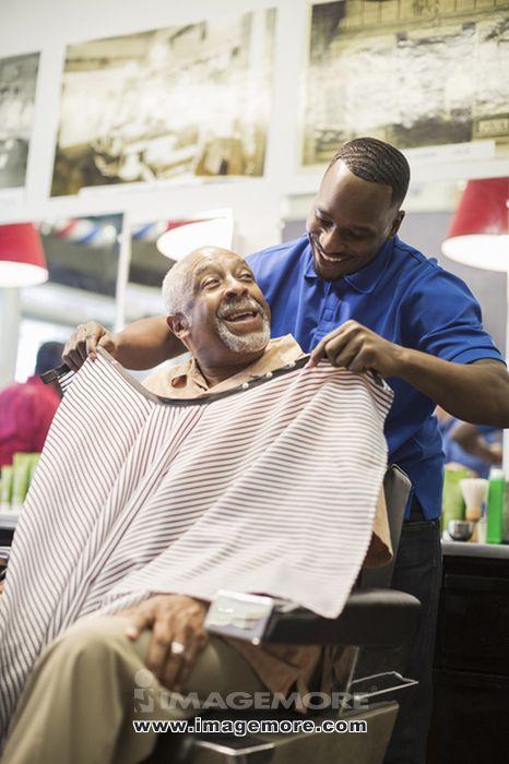 Black barber tying apron on customer in retro barbershop,