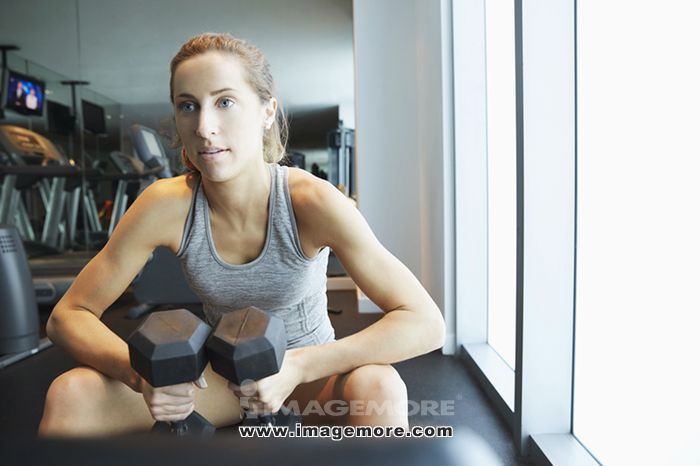 Serious woman lifting weights in gym,